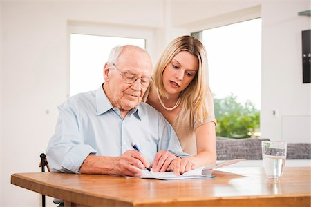 Young Woman and Senior Man looking at Document, Mannheim, Baden-Wurttemberg, Germany Stock Photo - Rights-Managed, Code: 700-06962186