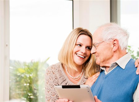 Young Woman and Senior Man using Tablet Computer at Home, Mannheim, Baden-Wurttemberg, Germany Stock Photo - Rights-Managed, Code: 700-06962199