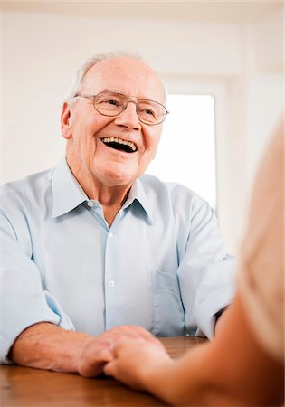 Senior Man Smiling and Talking to Young Woman at Home, Mannheim, Baden-Wurttemberg, Germany Stock Photo - Rights-Managed, Code: 700-06962192