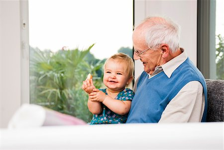 Senior Man with Baby Girl Sitting on his Lap at Home, Mannheim, Baden-Wurttemberg, Germany Stock Photo - Rights-Managed, Code: 700-06962201