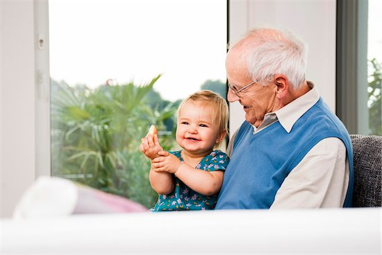 Senior Man with Baby Girl Sitting on his Lap at Home, Mannheim, Baden-Wurttemberg, Germany Stock Photo - Premium Rights-Managed, Artist: Uwe Umstätter, Image code: 700-06962201