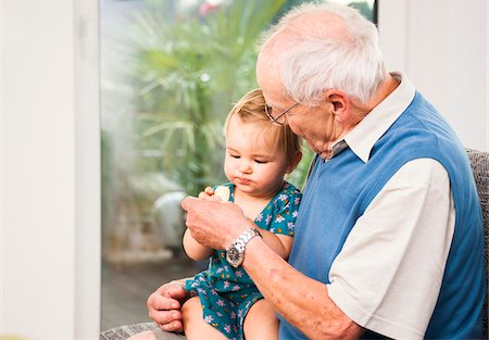 Senior Man with Baby Girl Sitting on his Lap at Home, Mannheim, Baden-Wurttemberg, Germany Stock Photo - Rights-Managed, Code: 700-06962202
