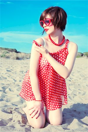 Young woman kneeling in sand on beach, wearing retro clothing, Italy Stock Photo - Rights-Managed, Code: 700-07066938