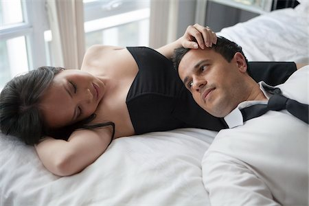 east asian - Couple laying on bed in formal wear, looking at each other Stock Photo - Rights-Managed, Code: 700-07067590