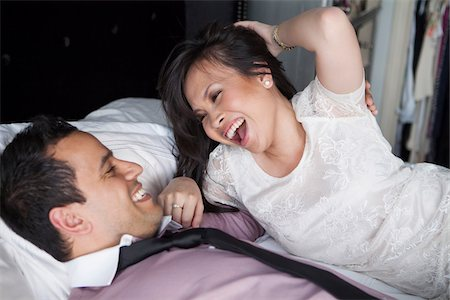 Close-up of couple laying on bed laughing Stock Photo - Rights-Managed, Code: 700-07062774