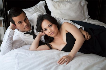 Portrait of couple laying on bed in formal wear, looking at camera Stock Photo - Rights-Managed, Code: 700-07062775
