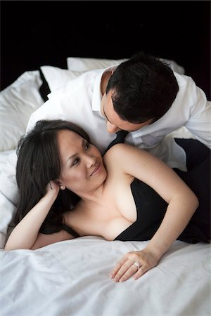 Close-up of couple looking at each other, laying in bed in formal wear Stock Photo - Rights-Managed, Code: 700-07062776