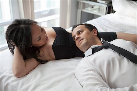 romantic couple bed - Couple laying in bed wearing formal wear, looking at each other Stock Photo - Rights-Managed, Code: 700-07062780