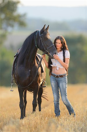 Young woman standing beside a Friesian horse in a cut cornfield, Bavaria, Germany Stock Photo - Rights-Managed, Code: 700-07080475