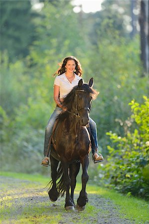 Portrait of a young woman riding a Friesian horse on a forest pathway, Bavaria, Germany Stock Photo - Rights-Managed, Code: 700-07108300
