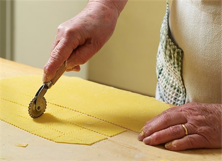 Close-up of elderly Italian woman making pasta by hand in kitchen, cutting pasta dough with rotary tool, Ontario, Canada Stock Photo - Rights-Managed, Code: 700-07108323