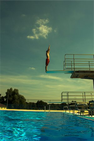 Teenage Boy Diving into Swimming Pool from Diving Board, Langenbeutingen, Baden-Wurttemberg, Germany Stock Photo - Rights-Managed, Code: 700-07117304
