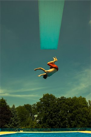 Teenage Boy Jumping into Swimming Pool from Diving Board, Langenbeutingen, Baden-Wurttemberg, Germany Stock Photo - Rights-Managed, Code: 700-07117307