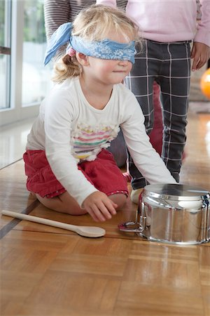Girl Sitting on Floor with Blindfold Playing Hit the Pot, Mulheim, North Rhine-Westphalia, Germany Stock Photo - Rights-Managed, Code: 700-07110694