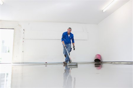 floor - Tradesman Working on new Floor Cover in Garage, Mulheim, North Rhine-Westphalia, Germany Stock Photo - Rights-Managed, Code: 700-07110692