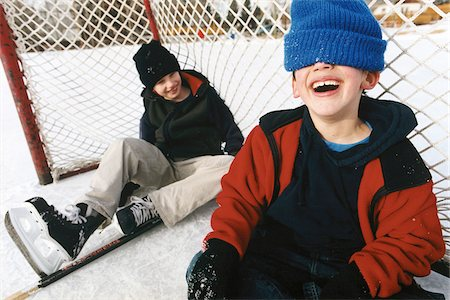 Two Boys Sitting in Hockey Net on Outdoor Ice Rink, Laughing Stock Photo - Rights-Managed, Code: 700-07199509