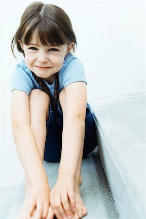 Portrait of Girl Sitting Outdoors Holding Feet Stock Photo - Rights-Managed, Code: 700-07199530