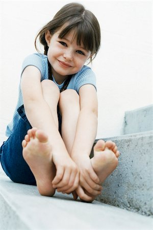 Portrait of Girl Sitting Outdoors Holding Feet Stock Photo - Rights-Managed, Code: 700-07199531