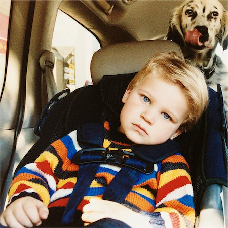 Portrait of Boy in Car Seat with Dog in Back of Car Stock Photo - Rights-Managed, Code: 700-07199549