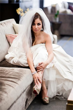 Portrait of bride sitting on sofa wearing wedding gown and veil, Ontario, Canada Stock Photo - Rights-Managed, Code: 700-07199831
