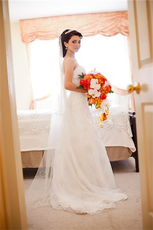 Portrait of bride wearing wedding gown and veil, standing in bedroom, looking at camera, Ontario, Canada Stock Photo - Rights-Managed, Code: 700-07199854