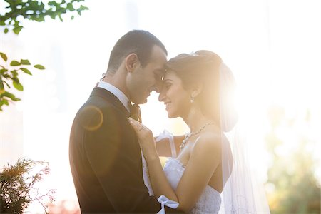 Close-up portrait of bride and groom standing outdoors, face to face, smiling and embracing, Ontario, Canada Stock Photo - Rights-Managed, Code: 700-07199860