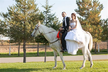 Bride and groom riding white horse together on wedding day, Ontario, Canada Stock Photo - Rights-Managed, Code: 700-07199863