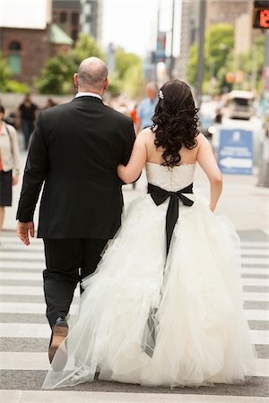 Backview of bride and groom walking across intersection of city street, Toronto, Ontario, Canada Stock Photo - Rights-Managed, Code: 700-07199882