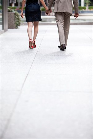 Backview of couple walking hand-in-hand down sidewalk on city street, Toronto, Ontario, Canada Stock Photo - Rights-Managed, Code: 700-07203957