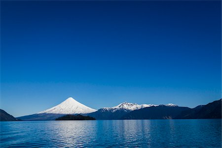 Scenic view of Todos los Santos Lake, with Osorno Volcano and mountain range in the distance, Parque Nacional Vicente Perez Rosales, Patagonia, Chile Stock Photo - Rights-Managed, Code: 700-07203981