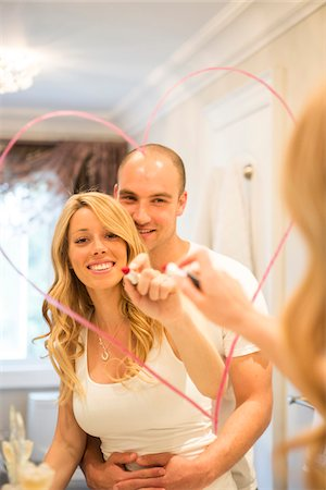 Young couple embracing and looking in bathroom mirror together, drawing a heart with lipstick on mirror, Canada Stock Photo - Rights-Managed, Code: 700-07237595