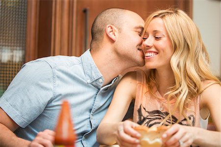 Young man kissing young woman on cheek, sitting and eating in home, Canada Stock Photo - Rights-Managed, Code: 700-07237598
