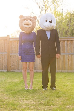 Portrait of couple standing in backyard dressed in formal attire, covering faces wearing costume bear heads, Canada Stock Photo - Rights-Managed, Code: 700-07237604