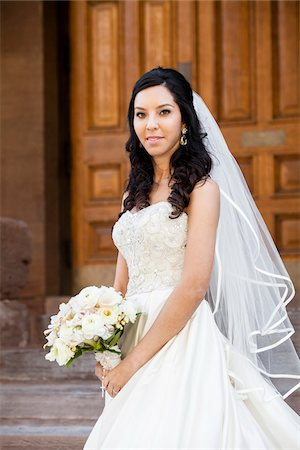 Close-up portrait of Bride in wedding gown holding bridal bouquet, standing on stairs in front of building, smiling and looking at camera on Wedding Day, Canada Stock Photo - Rights-Managed, Code: 700-07237617