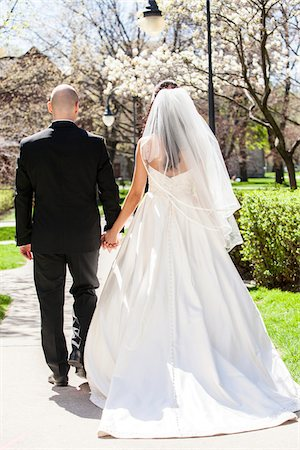 Backview of bride in wedding gown with bridegroom, holding hands and walking down pathway in park in Spring on Wedding Day, Canada Stock Photo - Rights-Managed, Code: 700-07237612