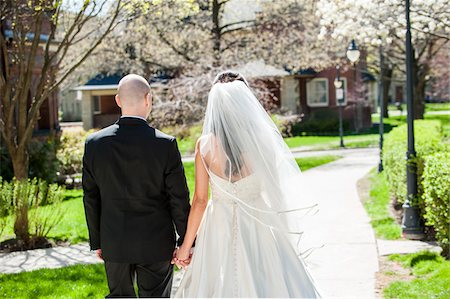 dark hair - Close-up of backview of bride in wedding gown with bridegroom, holding hands and walking down pathway in park in Spring on Wedding Day, Canada Stock Photo - Rights-Managed, Code: 700-07237627