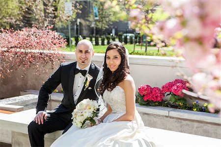 Portrait of Bride and groom sitting on stone bench in park in Spring, smiling and looking at camera, Canada Stock Photo - Rights-Managed, Code: 700-07237621