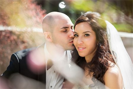 Close-up portrait of groom gving bride a kiss on cheek, sitting outdoors on Wedding Day, Canada Stock Photo - Rights-Managed, Code: 700-07237622