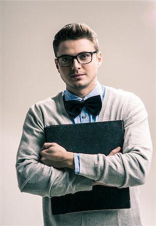 Portrait of Student wearing Bow Tie and Glasses with Binder, Studio Shot Stock Photo - Rights-Managed, Code: 700-07238144