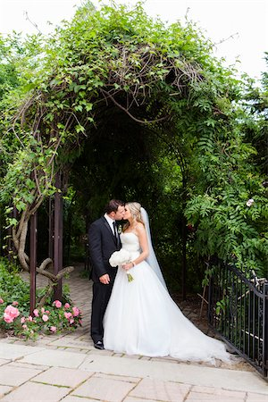 Bride and Groom standing outdoors under arbour, kissing on Wedding Day, Canada Stock Photo - Rights-Managed, Code: 700-07232326