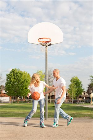 Couple playing basketball in neighbourhood park, Toronto, Ontario, Canada Stock Photo - Rights-Managed, Code: 700-07232340
