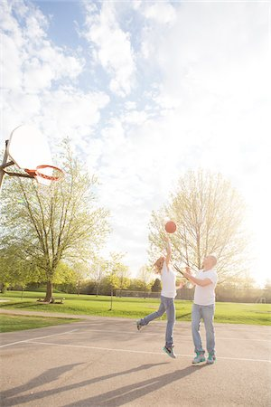 Couple playing basketball in neighbourhood park, Toronto, Ontario, Canada Stock Photo - Rights-Managed, Code: 700-07232341
