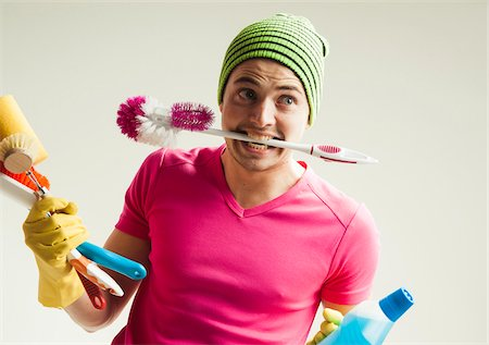 funny looking people - Close-up portrait of young man goofing around and holding colorful cleaning supplies, studio shot on white background Stock Photo - Rights-Managed, Code: 700-07278878