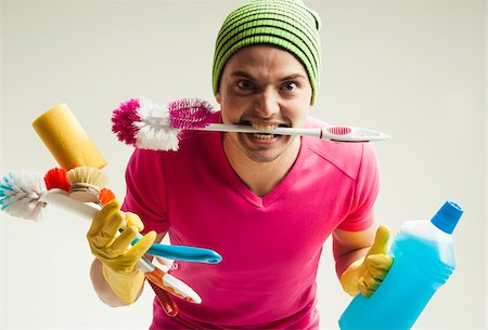 funny looking people - Close-up portrait of young man goofing around and holding colorful cleaning supplies, studio shot on white background Stock Photo - Rights-Managed, Code: 700-07278879