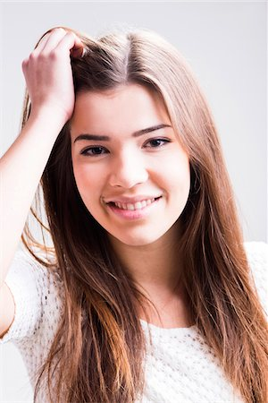 Close-up portrait of young woman with long, brown hair, smiling and looking at camera, studio shot on white background Stock Photo - Rights-Managed, Code: 700-07278966