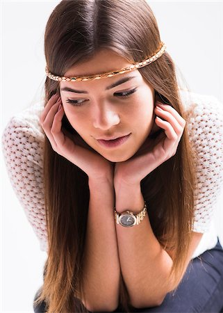 shimmering - Portrait of young woman with long, brown hair, wearing headband, leaning on elbows and looking downwards, studio shot on white background Stock Photo - Rights-Managed, Code: 700-07278969