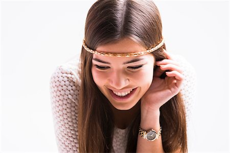 shimmering - Portrait of young woman with long, brown hair, wearing headband, smiling and looking downwards, studio shot on white background Stock Photo - Rights-Managed, Code: 700-07278970