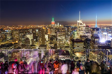 South Manhattan view of skyline with people at Top of the Rock Observation Deck, Rockefeller Center at dusk, with Empire State Building illuminated with colours of the Italian flag, Columbus Day, Midtown, Manhattan, New York City, New York, USA Stock Photo - Rights-Managed, Code: 700-07310313