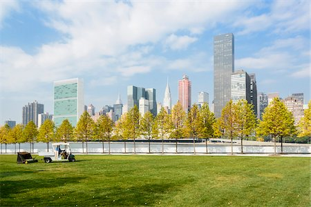 Grounds keeper on Roosevelt Island with view of Midtown skyline with United Nations Building, in Autumn, Manhattan, New York City, New York, USA Stock Photo - Rights-Managed, Code: 700-07310331
