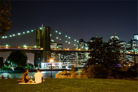 sitting under tree - People sitting on grass in park, Downtown Manhattan skyline with Brooklyn Bridge illuminated at night, Manhattan, New York City, New York, USA Stock Photo - Rights-Managed, Code: 700-07310876